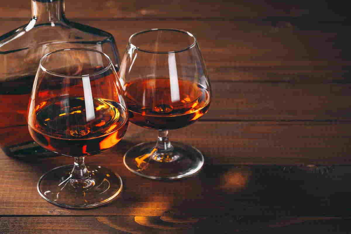 Due bicchieri di cognac con bottiglia dietro
