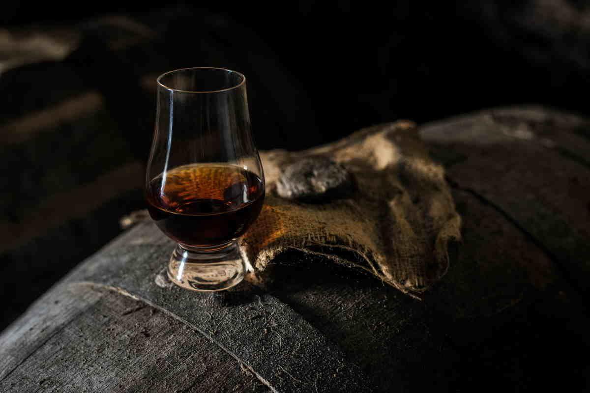 Bicchiere di whisky su botte