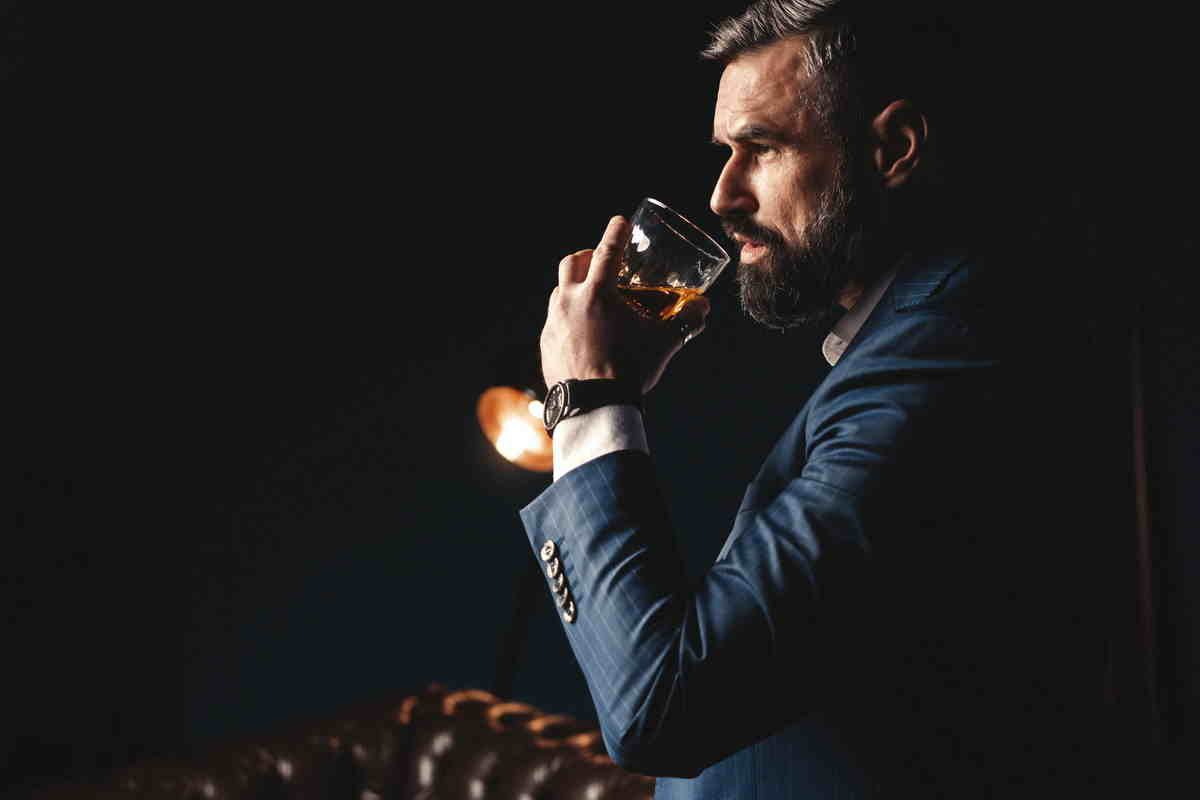 Uomo degusta whisky